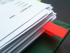 A stack of papers, a few sheets marked with red tabs.