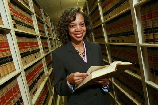 Faculty member with book at library