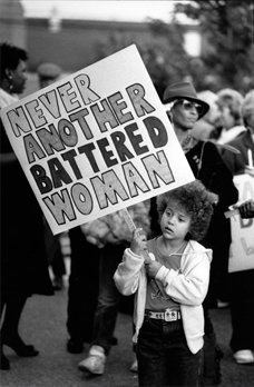 Young girl at a protest holding a sign reading 'Never another battered woman'