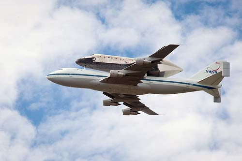 The Space Shuttle Discovery, piggybacking on the Shuttle Carrier Aircraft, in flight.