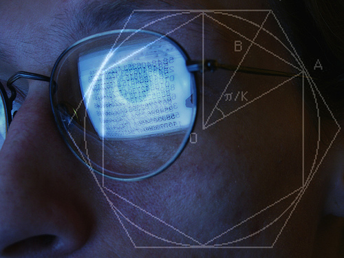 A man looks at a computer screen, reflected in his glasses. A geometrical diagram is superimposed over the photo.
