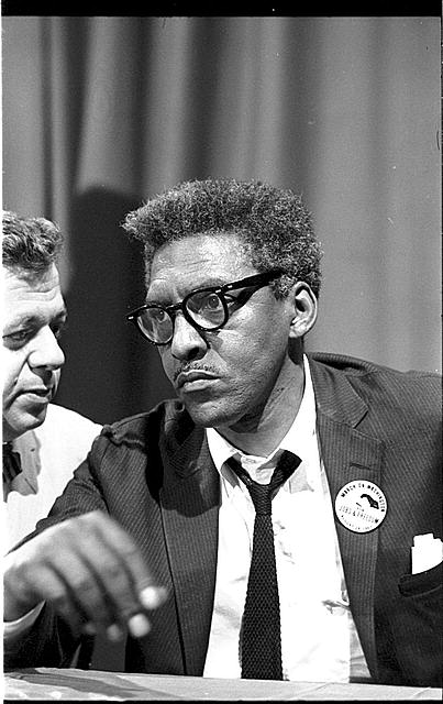 photo, Bayard Rustin at news briefing on the Civil Rights March on Washington in the Statler Hotel, half-length portrait, seated at table