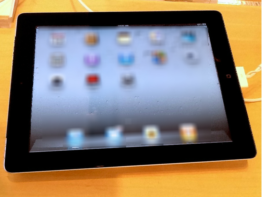 A black iPad showing blurred icons on its screen.