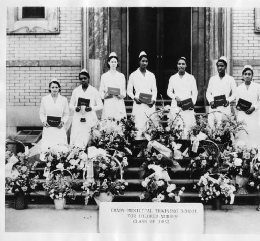 Graduates of the Grady Municipal Training School for Colored Nurses holding their diplomas in front of the Albert Steiner Ward, Atlanta, Georgia, 1930.