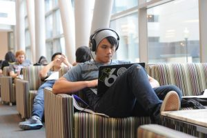 Student in the library using a laptop wearing headphones